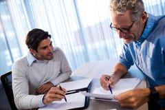 2 бизнесмена читая документ и взаимодействуя Стоковое Изображение RF