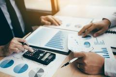 2 бизнесмены анализируя общие отчеты о диаграммы операционных расходов дела и используя вычисление выгоды калькулятора в стоковое фото rf