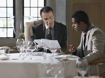Бизнесмены анализируя документы на таблице ресторана Стоковое Изображение
