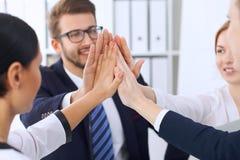 Бизнесмены бизнесменов группы собирают счастливую показывая сыгранность и соединяя руки или давать 5 после подписания Стоковые Изображения