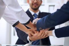 Бизнесмены бизнесменов группы собирают счастливую показывая сыгранность и соединяя руки или давать 5 после подписания Стоковая Фотография