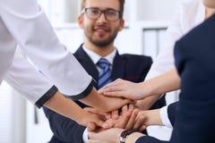 Бизнесмены бизнесменов группы собирают счастливую показывая сыгранность и соединяя руки или давать 5 после подписания Стоковое Изображение