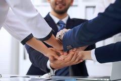 Бизнесмены бизнесменов группы собирают счастливую показывая сыгранность и соединяя руки или давать 5 после подписания Стоковое Изображение RF
