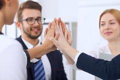 Бизнесмены бизнесменов группы собирают счастливую показывая сыгранность и соединяя руки или давать 5 после подписания Стоковые Изображения RF