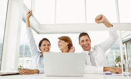 Бизнесмены веселя перед компьтер-книжкой на офисе Стоковые Изображения