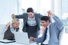 Бизнесмены веселя перед компьтер-книжкой на офисе Стоковые Фото