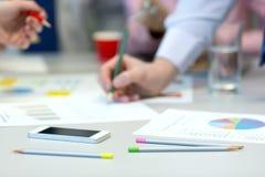 Бизнесмены взаимодействия - таблицы офиса с диаграммами и руками людей Стоковое Изображение