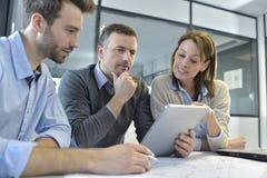 Бизнесмены встречая и обсуждая новый проект на таблетке Стоковое Изображение RF