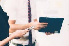 Бизнесмены встречая крупный план руки женщины держа smartphone Стоковые Изображения