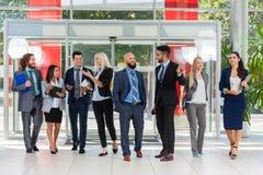Бизнесмены встречи группового обсуждения, улыбки говоря в современном офисе, команде коллеги предпринимателей Стоковые Фото
