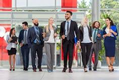 Бизнесмены встречи группового обсуждения, улыбки говоря в современном офисе, коллеге предпринимателей Стоковая Фотография RF