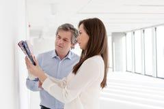 Бизнесмены выбирая образцы цвета против стены в пустом офисе Стоковые Изображения