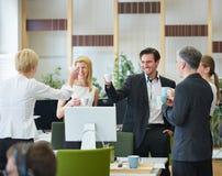 Бизнесмены выпивая кофе в офисе Стоковая Фотография