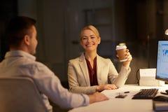 Бизнесмены выпивая кофе на офисе ночи Стоковые Фотографии RF