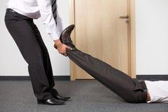 Бизнесмены вытягивая ногу коллеги на офисе Стоковые Фото