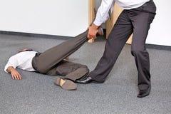 Бизнесмены вытягивая ногу коллеги на офисе Стоковые Изображения