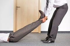 Бизнесмены вытягивая ногу коллеги на офисе Стоковые Изображения RF