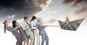 Бизнесмены вытягивая шлюпку доллара бумажных денег Стоковые Фотографии RF