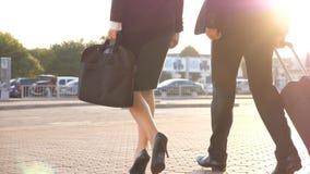 Бизнесмены выходят аэропорт и идти с их багажом на улицу города Непознаваемые человек и женщина в пятках акции видеоматериалы