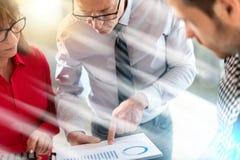 Бизнесмены в встрече обсуждая о финансовых результатах, световом эффекте Стоковое фото RF