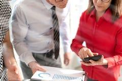 Бизнесмены в встрече обсуждая о финансовых результатах, влиянии световых лучей Стоковые Изображения RF