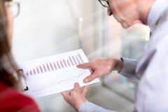 Бизнесмены в встрече обсуждая о финансовых результатах, влиянии световых лучей Стоковое Фото