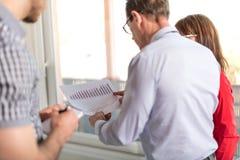 Бизнесмены в встрече обсуждая о финансовых результатах Стоковое фото RF