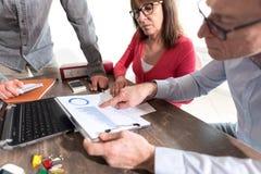 Бизнесмены в встрече обсуждая о финансовых результатах Стоковые Изображения RF