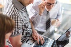 Бизнесмены в встрече работая на компьтер-книжке, влиянии световых лучей Стоковое фото RF