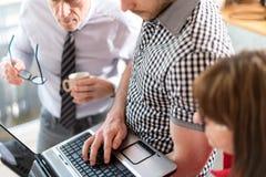 Бизнесмены в встрече работая на компьтер-книжке Стоковые Фотографии RF
