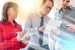 Бизнесмены в встрече работая на таблетке, overlaid с сетью, световой эффект Стоковые Изображения