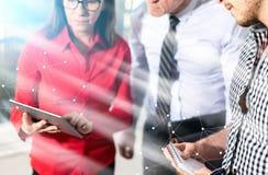 Бизнесмены в встрече работая на таблетке, overlaid с сетью, световой эффект Стоковые Изображения RF