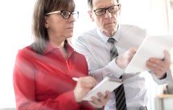 Бизнесмены в встрече работая на таблетке, влиянии световых лучей Стоковые Изображения RF