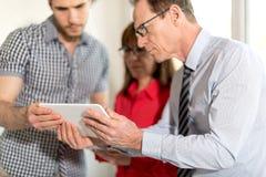 Бизнесмены в встрече работая на таблетке Стоковое Изображение