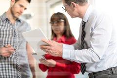 Бизнесмены в встрече работая на таблетке, overlayed с лучами Стоковая Фотография RF