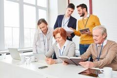 Бизнесмены в вычисляя семинаре Стоковое фото RF