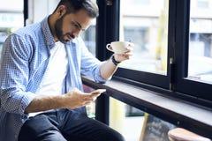Бизнесмены в голубой рубашке используя беспроводную связь к интернету в зоне wifi кафа Стоковое Изображение