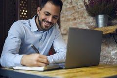 Бизнесмены в голубой рубашке используя современный портативный компьютер и wifi в coworking космосе стоковые изображения