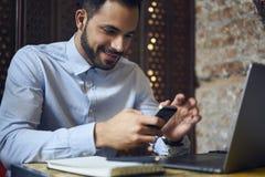 Бизнесмены в голубой рубашке используя smartphone соединились к беспроволочному интернету в кафе Стоковое Изображение