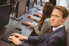 Бизнесмены в компьютерной комнате усмехаясь на камере Стоковая Фотография RF