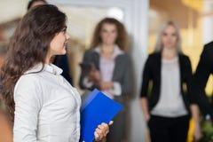 Бизнесмены в лобби, гости гостеприимсва администратора гостиницы группы предпринимателей гонки смешивания приезжают Стоковое фото RF