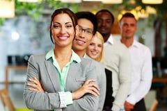 Бизнесмены в офисе выровнянном вверх Стоковые Фото