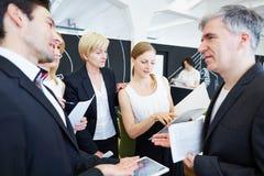 Бизнесмены в офисе говоря друг к другу Стоковое Фото