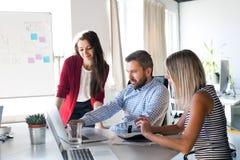 3 бизнесмены в офисе говоря совместно Стоковое фото RF
