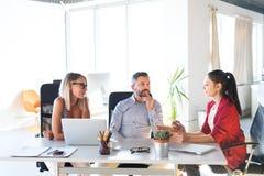 3 бизнесмены в офисе говоря совместно Стоковые Изображения RF