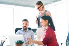 3 бизнесмены в офисе говоря совместно Стоковое Изображение