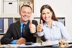 Бизнесмены в офисе держа большие пальцы руки вверх Стоковое фото RF