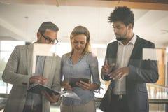 Бизнесмены в офисе имея переговор и использование цифровые Стоковое Изображение RF
