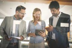 Бизнесмены в офисе имея переговор и использование цифровые Стоковая Фотография RF
