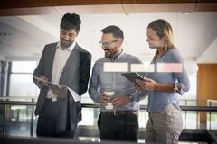 Бизнесмены в офисе имея переговор и использование цифровые Стоковая Фотография